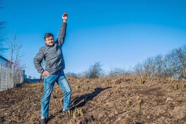 Jahnsdorfs Baumschutzbeauftragter Mike Löffler zeigt, wie hoch die Hecke einst gewesen ist. Nun ist alles platt. Er hat sich bei der Gemeinde beschwert, die eigentlich mit ihm zusammenarbeitet.
