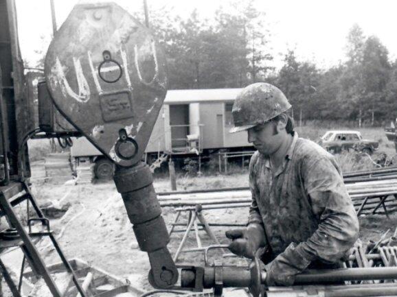 Ein Kollege der Erkundungstruppe baut ein Bohrgestänge an eine Umlenkrolle, die im Wismut-Jargon Uhu genannt wurde. Solche Bohrgeräte waren auf sowjetischen Lkw montiert. Leichte Geräte auf Sils bohrten um die 200 Meter tief, mittlere auf Ural-Fahrzeugen etwa 500 Meter.