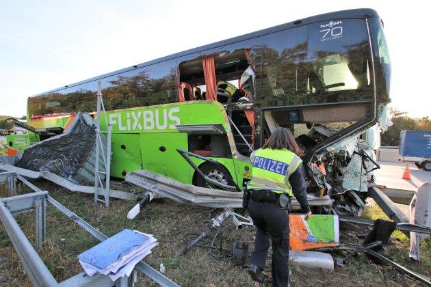 Polizisten arbeiten an einer Unfallstelle, an der ein Reisebus des Fernreiseunternehmens Flixbus auf der Autobahn 5 (A5) an der Abfahrt zur Tank- und Rastanlage Bruchsal in einen Fahrbahnteiler geprallt war.