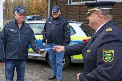 Polizeipräsident René Demmler (r.) übergibt an drei der insgesamt fünf neuen Sicherheitswächter die Urkunden. Nach der Ausbildung müssen sie nun selbstständig in Wohngebieten und Parkanlagen auf Streife gehen.