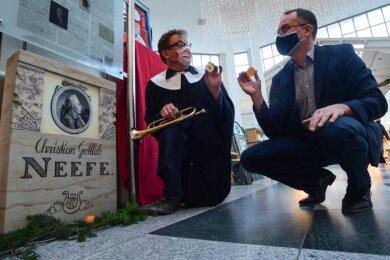 Joachim Zehme (links) und Christoph Koop hocken vor dem neuen Denkmal für Komponist Christian Gottlob Neefe. In den Händen halten sie Neefe-Taler aus Schokolade, die zur Einweihung verteilt werden sollen.