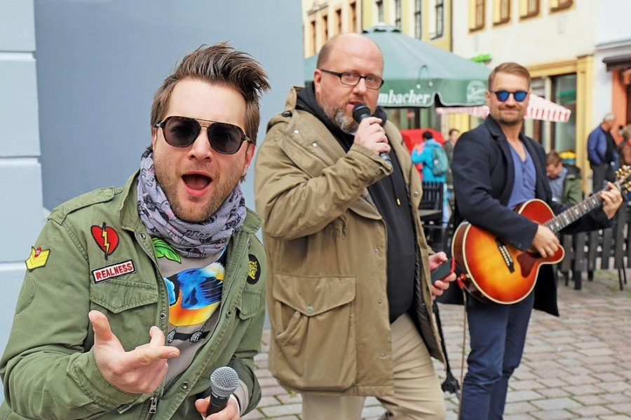 Tim Gernitz (l.) und Felix Günther (r.) von den Notendealern unterstützten Marcus Poschlod (Mitte) bei seinem Versuch, mit Gesang Geld zu verdienen.