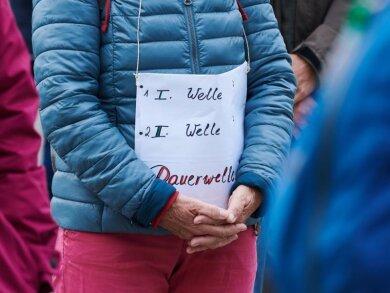«1.Welle - 2.Welle - Dauerwelle» steht auf dem Plakat einer Demonstrantin bei einer Querdenken-Demo.
