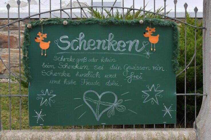 Die Freibergerin Heike Grütze hat den Vorgarten der Silbermann-Grundschule geschmückt und eine Tafel weihnachtlich verziert.