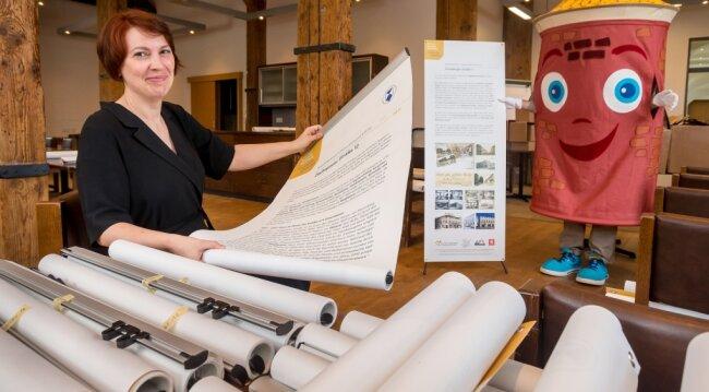 Susann Hofmann, Amtsleiterin für Kultur und Tourismus der Stadt Marienberg, zeigt gemeinsam mit Fest-Maskottchen Uli zwei der insgesamt 78 zur Marienberger Handelsgeschichte entstandenen Banner.