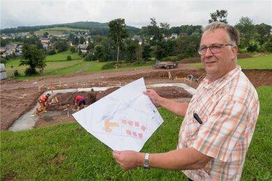 Feriendorf-Investor Matthias Lorenz mit einem Bauplan an der Baustelle des ersten Ferienhauses.