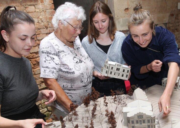 Die Studentinnen Sarah Pens, Lisa Lipfert und Agnes Schulz-Bongert mit Besucherin Christel Magdziacz vom Verein Land Vogtland vor dem Modell des Liebauer Herrenhauses.