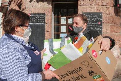 """Ingo Kübeck vom Verein verteilt die neuen """"Kollektüten"""" an Läden in Chemnitz, wie hier an die Fleischerei Thiele mit Inhaberin Elke Seitz."""