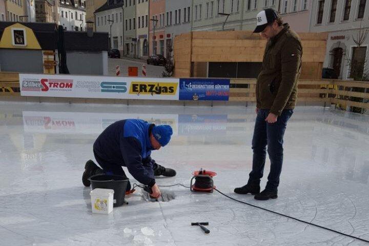 Mitarbeiter der Stadtwerke flicken das gut 30 Zentimeter große Loch in der Eisdecke.