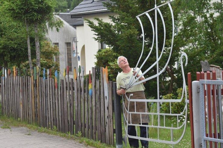Johannes Tauscher vor seinem selbst geschmiedeten Gartentor. Bei Spaziergängern komme das Kunstwerk gut an, sagt er.