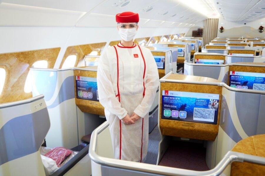 Sicherheit geht vor: Die Flugbegleiterin trägt über ihrer Uniform persönliche Schutzausrüstung.