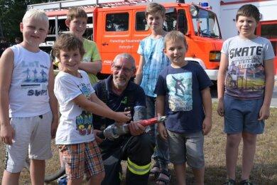 """Jörg Zappner (Mitte), Wehrleiter der Feuerwehr Hohndorf, hat gemeinsam mit den Kindern aus dem Feuerwehr-Camp - Rafael Stüber, Niclas Beyer, Tim Gränitz, Emil Spölders, Oskar Olschowsky und Tino Schönbach (von links) - den Schlauch für den Schnellangriff aus dem Löschfahrzeug (hinten) ausgerollt. Dieser Wagen ist eine Dauerleihgabe der Feuerwehr für das Floriansdorf im Kiez """"Am Filzteich""""."""