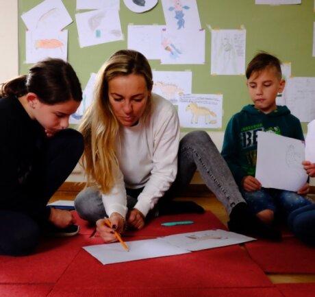 Von der Skizze bis zu Bildern in Tusche oder Aquarell: Kursleiterin Sandra Hofmann-Trepák mit Teilnehmern der Ferienfreizeit. Die Kinder entwerfen Fabeltiere - in der Tradition mittelalterlicher Bestiarien.