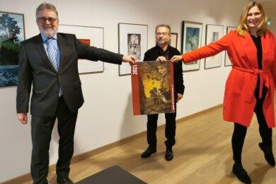 Der Chef der Zwickauer Energieversorgung Volker Schneider, Kunstvereinsvorsitzender Wolfgang Schinko und Zwickaus OB Constance Arndt zeigen den neuen Kalender des Zwickauer Kunstvereins.