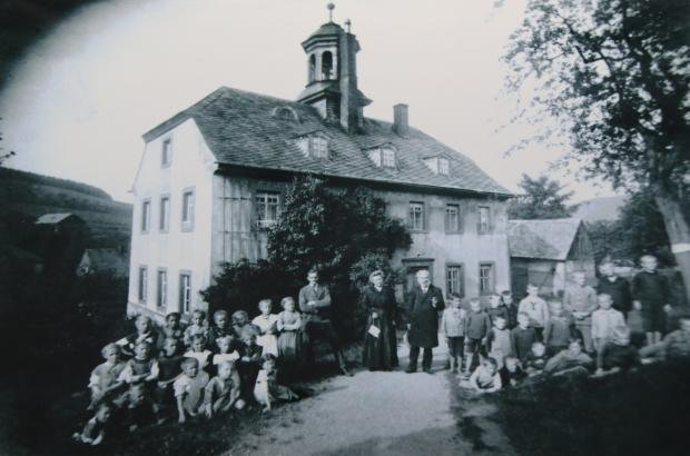 Aufnahme der Hennersdorfer Schule: Das Bild muss vor 1924 fotografiert worden sein, weil in dem Jahr ein Anbau hinzukam.