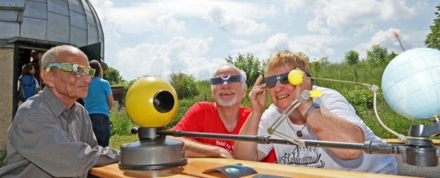 Mit dem Rücken zur Sonne - nur fürs Foto: Die Astronomiefreunde Erhard Liebold (links) sowie Jürgen und Monika Müller haben zur Sonnenfinsternis ein Modell aufgebaut, das das Himmelsereignis verdeutlicht.