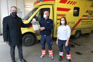 Oberbürgermeister Sven Krüger überreicht ein Geschenk an Rene Freudrich und Celeste Rochlitzer vom Malteser Hilfsdienst.