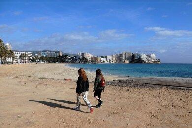 Zwei junge Frauen gehen am leeren Strand von Magaluf entlang. Mallorca gilt seit Freitag nicht mehr als Corona-Risikogebiet.