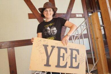 Dorothee Obst mit Cowboy-Hut und Fan-Shirt sowie einem Schild mit Autogrammen der Bandmitglieder.