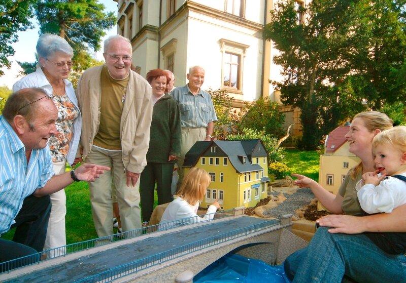 """Kurt Langer, Mitinitiator des Festes (l.), erklärt Besuchern das vor der Villa im Park aufgebaute """"Klein Gückelsberg""""."""
