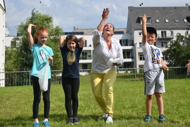 """In der Hübschmannstraße auf dem Kaßberg, am Verlagssitz der BL Media und von Grimms & Co., fliegen """"Blumenbomben"""" durch die Luft. Die Erstklässler Nora, Lotta und Phil von der Grundschule Rabenstein haben mit Bianka Lebsuch (3. von links) viel Spaß."""