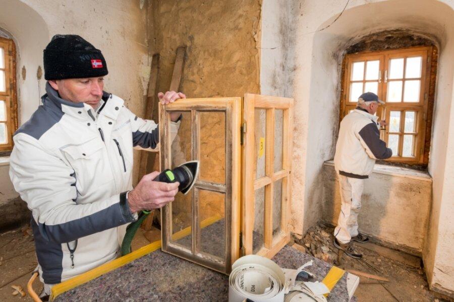 Maler Sven Lohs und dessen Kollege Steffen Wagner (v.l.) arbeiten derzeit die Schlossfenster auf. Nach dem Abschleifen erhalten sie einen neuen Anstrich, der aus Grundierung und Lasur besteht.