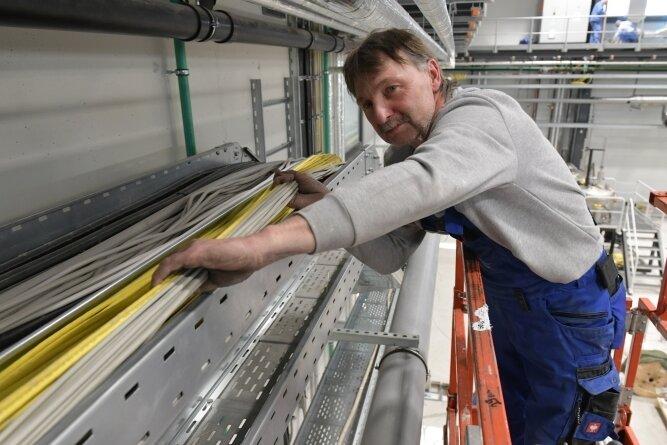 Jürgen Brunzel von der Firma Rendke aus Großenhain verlegt Kabel in der Halle. Neben der Stromversorgung muss auch der Datenfluss funktionieren.