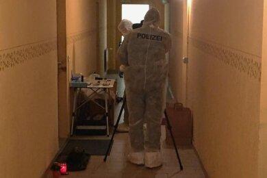 Kriminaltechniker der Polizei sicherten Spuren vor der Tür der Wohnung, in der ein 58-Jähriger tot aufgefunden worden war. Als Zeichen der Trauer hat jemand Grablichter neben die Tür gestellt.