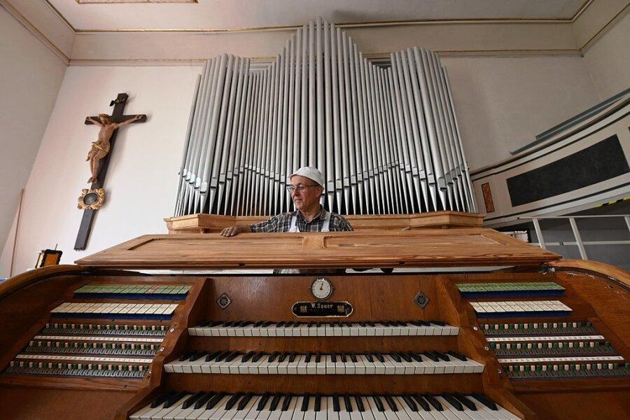 Malermeister Andreas Petzold hat die Holzteile der Sauer-Orgel in der Burgstädter Stadtkirche saniert. Dabei wurde originalgetreu die Kiefer-Maserung durch eine Lasur herausgearbeitet und zuvor der deckende Anstrich entfernt. Hier setzt er den Schlussdeckel am Spieltisch.
