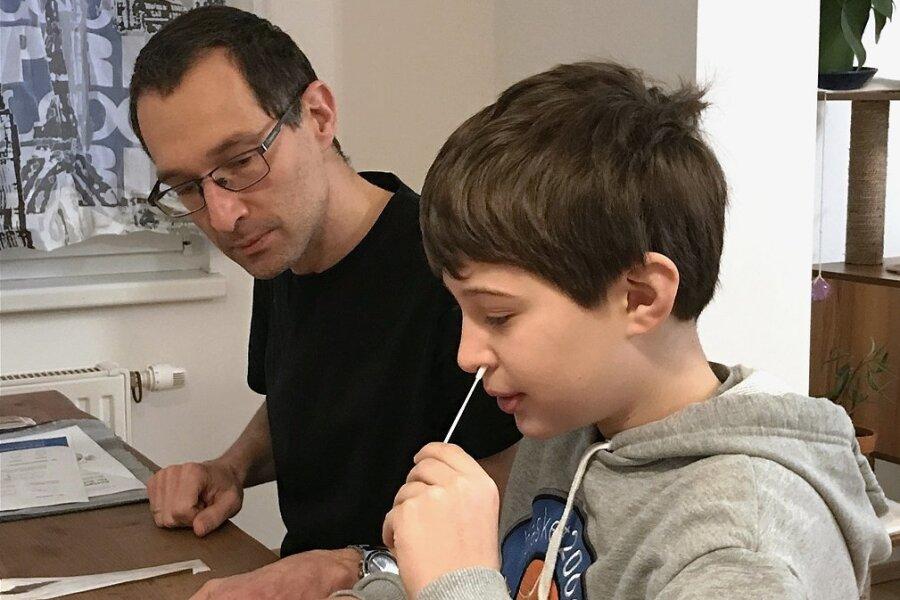 In Österreich bereits Praxis: Der neunjährige Tim führt unter der Aufsicht seines Vaters einen Corona-Selbsttest durch.