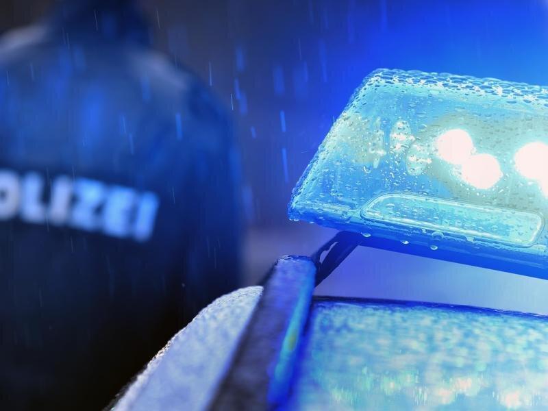 Ein Polizist steht vor einem Streifenwagen mit Blaulicht.