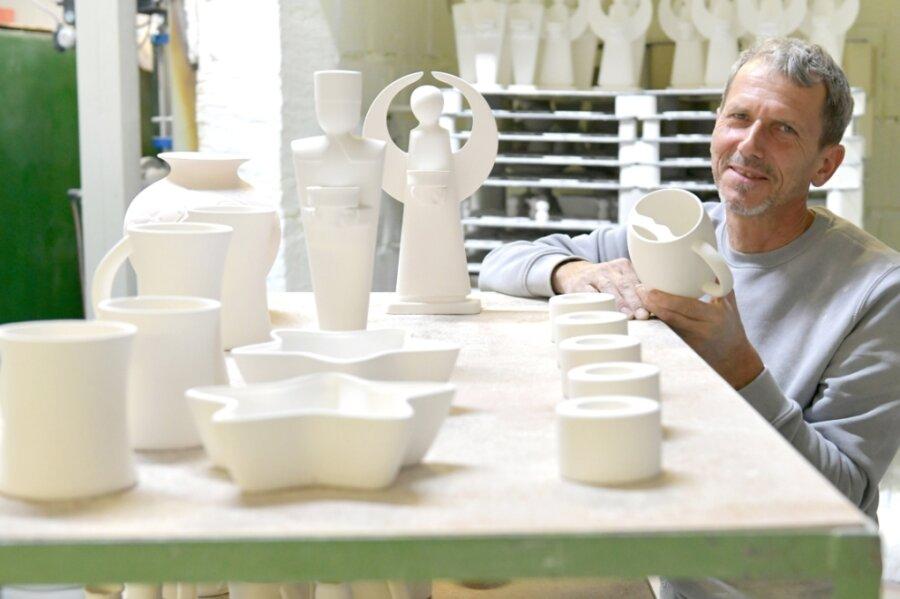 Neben Kaffeeservices ist derzeit die Barttasse sehr gefragt. Die Tasse ist so konstruiert, dass der Oberlippenbart beim Trinken unberührt bleibt. Andreas Richter, Produktionsleiter im Freiberger Porzellanwerk, hält eine Form davon in den Händen. Zu den Rennern im Weihnachtsgeschäft zählen auch Engel und Bergmann.