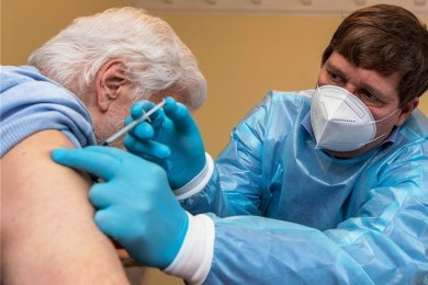 Der Rochlitzer Allgemeinmediziner Dr. Martin Grzelkowski impft einen älteren Mann in der Tagespflege der Sozialservicegesellschaft.