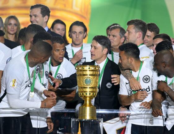 Trainer Niko Kovac (M) von Eintracht Frankfurt und seine Spieler jubeln über dem Sieg hinter dem Pokal bei der Siegerehrung auf dem Podium.