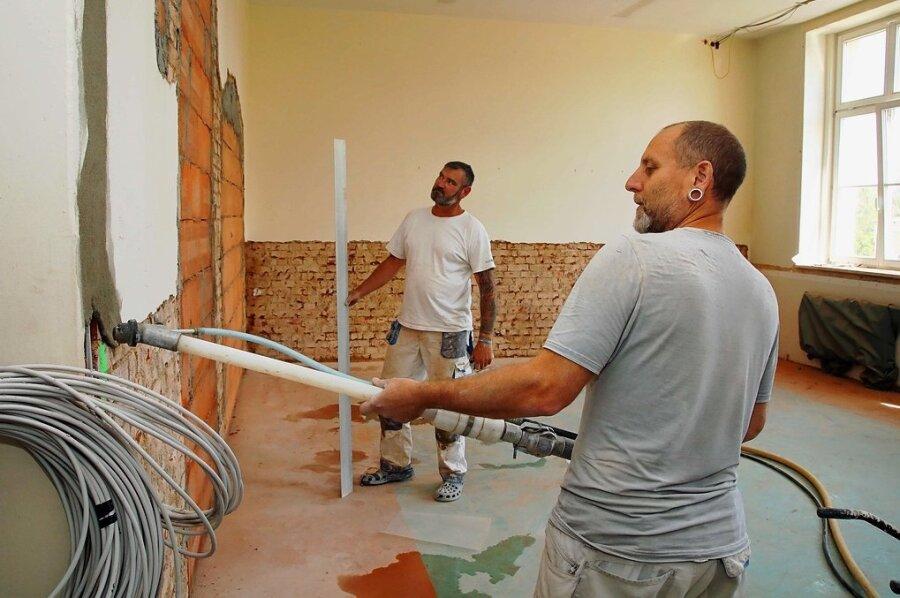 Thomas Thümmel (r.) und Daniel Hajdu, Mitarbeiter einer Chemnitzer Baufirma, sind in einem Unterrichtszimmer zugange.