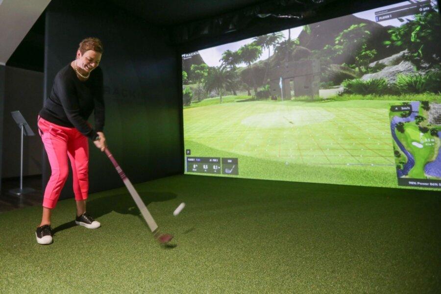 """Peggy Fritzsche, Reporterin bei der """"Freien Presse"""", spielt gern Golf. Nun testete sie die neue, digital gestützte, Indoor-Anlage im Chemnitzer Sportforum. Zuerst spielte sie auf einem englischen Platz. Für dieses Foto schwang sie den Schläger, um auf einem Golfplatz in Florida zu spielen. Eine Stunde in einer der insgesamt drei eingerichteten Spielboxen kostet für vier Personen 40 Euro, Spieler vom Golfplatz Klaffenbach zahlen 32 Euro pro Stunde."""