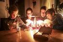 Malte (11), Kira (14), Mutter Katja und Kalle (9) aus Geyer spielen zusammen Karten und machen das Beste aus dem Stromausfall.