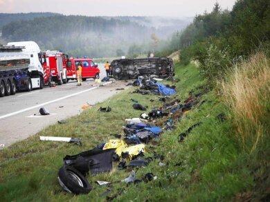 Trümmerteile liegen an der Unfallstelle neben der Autobahn 9, im Hintergrund liegt der umgestürzte Transporter.