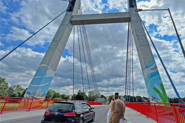 """Am Betonpylon der Schlunziger Brücke wurden jetzt Graffiti aufgebracht. Das soll nicht nur als Blickfang dienen. Von dieser Bemalung erhofft man sich auch, dass es Schmierereien, wie sie schon wenige Tage nach der Verkehrsfreigabe der Brücke im vorigen Jahr an dieser zu sehen waren, nicht mehr gibt. """"Die Entfernung war jedes Mal mit großem Aufwand verbunden und verursachte meist Kosten im vierstelligen Bereich"""", sagt der Beigeordneter Carsten Michaelis (CDU). Zu Jahresbeginn sei die Idee geboren worden, mit der künstlerischen Gestaltung den Pylon vor weiteren Besprühungen zu schützen. Aus verschiedenen Entwürfen des Künstlers Maik Detzner, der auch die """"Schwibbogen""""-Stützwand in Ortmannsdorf gestaltet hat, fiel die Entscheidung auf ein Motiv, das den dörflichen Charakter im Sommer und Herbst widerspiegelt. Kosten: circa 5000 Euro.ja"""