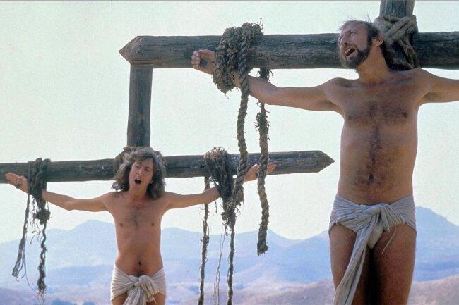 """""""Folgt der heiligen Flasche!"""" Die Schauspieler Eric Idle und Graham Chapman von der britischen Komikergruppe Monty Python singen in der Kreuzigungsszene aus der bissigen Kino-Religionssatire """"Das Leben des Brian"""" von der Sonnenseite des Lebens."""