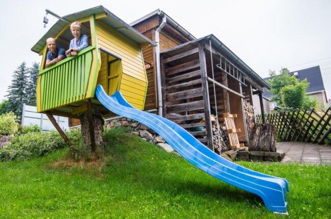 Stefan und Anett Friedel schauen aus dem Baumhaus, das im vergangenen Jahr für die Enkel Felix und Jonas entstanden ist.