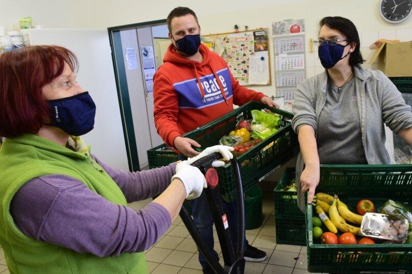 Die Mitarbeiter der Chemnitzer Tafel Tamara Bartel, Rafael Kraft und Anja Rahn (von links) haben die neuen Masken gleich nach der Übergabe angezogen und sortieren damit Lebensmittel.