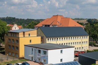 Blick auf die Gebäude (orange und gelb), in denen die Arbeitsagentur und das Jobcenter untergebracht waren. Dahinter ist das Dach der Regenbogen-Grundschule zu sehen.