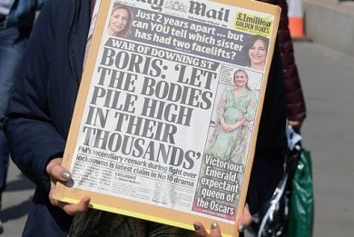 """Eine Demonstrantin hält eine Titelseite der britischen Zeitung """"Daily Mail"""" vor dem Cabinet Office, eine zentrale Regierungsbehörde, in London mit einem angeblichen früheren Zitat von Johnson hoch. """"Boris: ,Let the bodies pile high in their thousands'"""" (übersetzt: """"Lasst die Leichen sich zu Tausenden auftürmen"""")."""