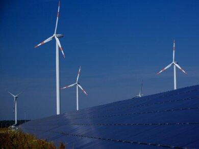 Windräder zur Stromerzeugung drehen sich in Mecklenburg-Vorpommern hinter einem Solarpark.