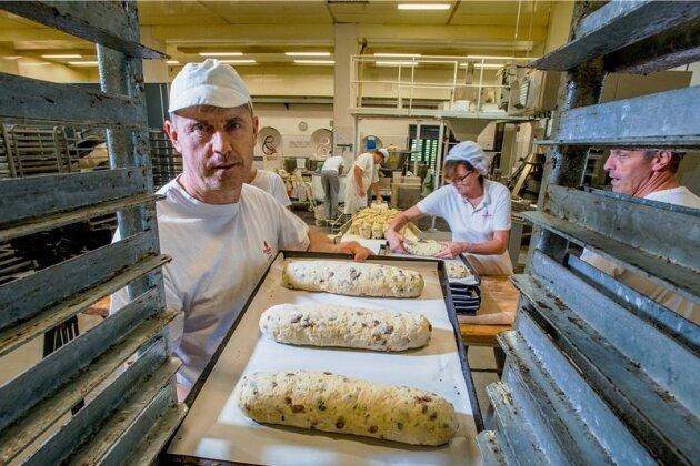 Kay Blaschke ist einer der Bäcker, die aus dem Teig per Hand Stollen formen. Mehr als 100 Stück gehen pro Stunde durch seine Hände.