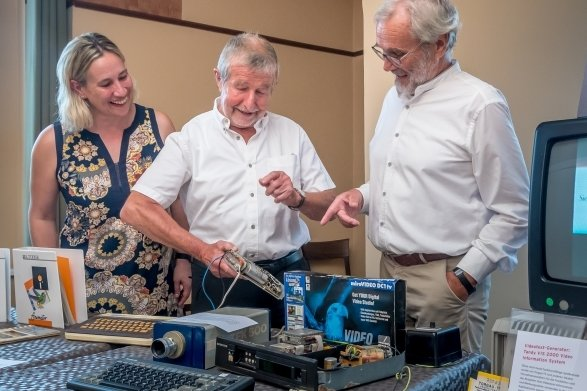 Zur Ausstellungseröffnung zeigte Günter Rötzer (M.) den Medienwissenschaftlern Dr. Judith Kretzschmar und Prof. Dr. Rüdiger Steinmetz Technik, mit der er Ende der 1980er-Jahre zunächst Texttafeln erstellte und ins Kabelnetz einspeiste.