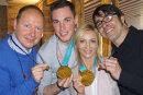 Die Eiskunstläufer Aljona Savchenko und Bruno Massot überreichen ihren Trainern Alexander König und Jean-Francois Ballester (rechts) extra angefertigte Replikas ihrer olympischen Goldmedaillen.