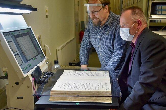 Der aktuelle Leiter des Limbach-Oberfrohnaer Stadtarchivs Christian Kirchner (hinten) zeigt dem künftigen Leiter Heiko Bohmann das Gerät zur Digitalisierung von Dokumenten aus Papier.