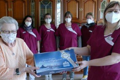 Mit einem Stollen bedankt sich Susi Decker, die in der betreuten Wohnanlage der Sozialbetriebe Mittleres Erzgebirge in Zschopau zuhause ist, bei Sindy Dienelt und dem gesamten Pflegeteam für die Unterstützung.